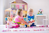 Adorable kids playing with stuffed animals and doll house