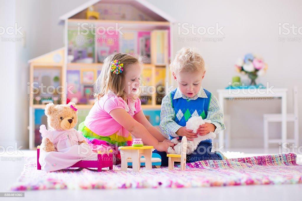 Adoráveis crianças brincando com animais de pelúcia e Casa de boneca - foto de acervo