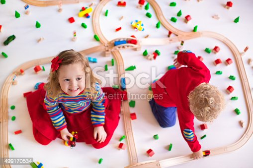 istock Adorable kids playing with wooden train set 499170534