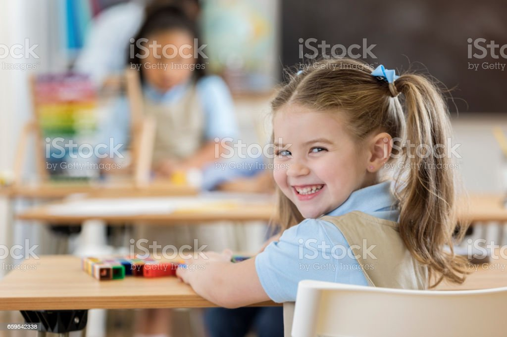 Adorable kindergartner in class stock photo
