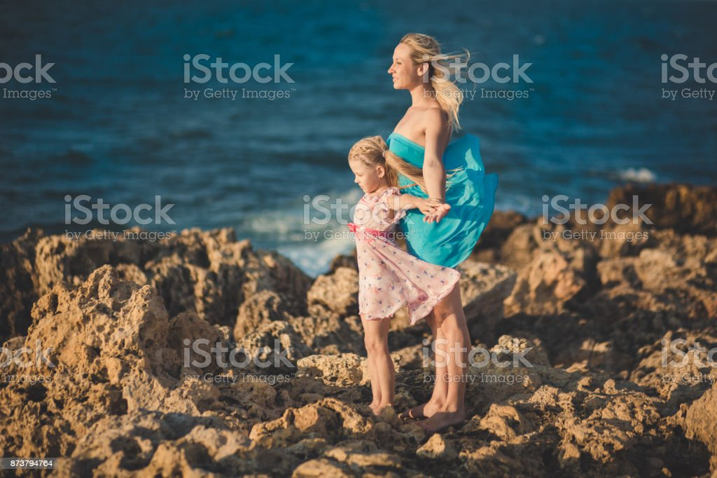 Adorable lady mother sitting on rocks beach in light blue dress together with her cute little blond daughter wearing pink airy dress enjoying time weekend together family and sea ocean. stock photo