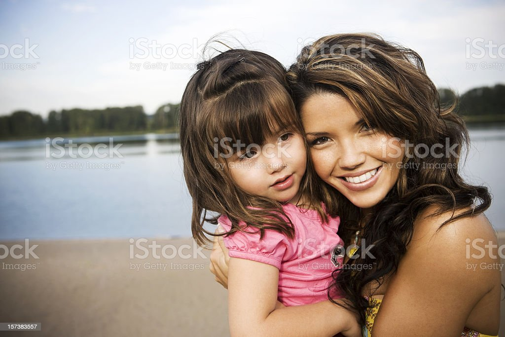 Adorable Latina Mom and Daughter Embracing on Beach, Copy Space royalty-free stock photo