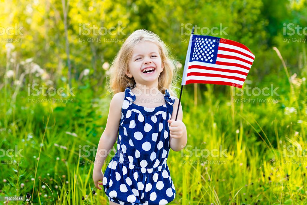 Adorable laughing little girl holding american flag and waving it stock photo