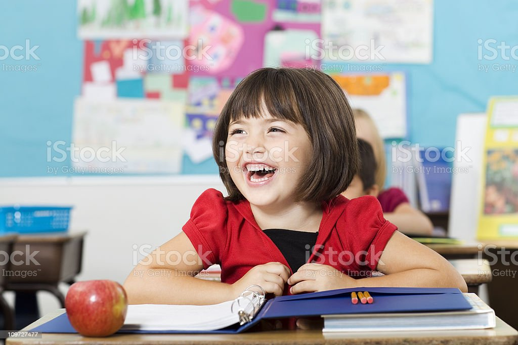 Adorable Laughing Little Girl in Elementary Classroom, Copy Space royalty-free stock photo