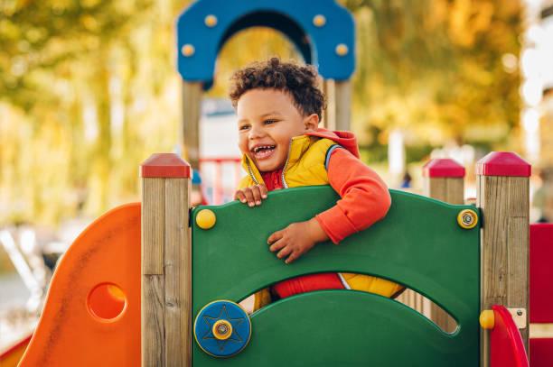 Entzückenden kleinen 1-2 Jahre alten Kleinkind Jungen Spaß am Spielplatz, Kind tragen orange Hoodie Jacke und gelbe Weste – Foto