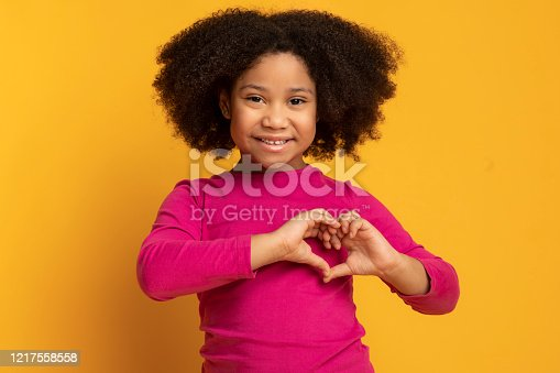 Love Concept. Adorable Little African American Girl Showing Heart Gesture With Hands Over Yellow Background In Studio, Free Space