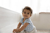 istock Adorable little african baby relying on furniture, making first steps. 1271954622