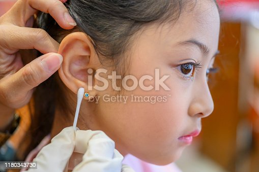 Adorable little Asian girl having ear piercing process.
