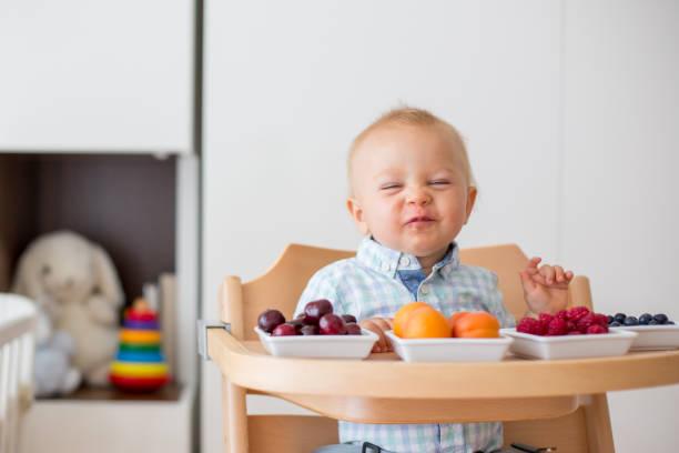 Adorable bebé niño, comer frutas frescas en el hogar - foto de stock
