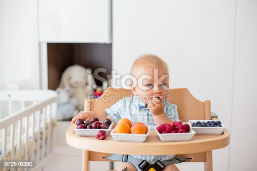 Adorable little baby boy, eating fresh fruits at home, sitting in baby chair in kids room