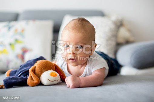 istock Adorable little baby boy, playing with toy, looking curiously at camera 858117986