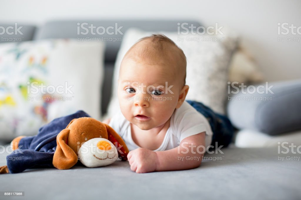 Adorable little baby boy, playing with toy, looking curiously at camera stock photo