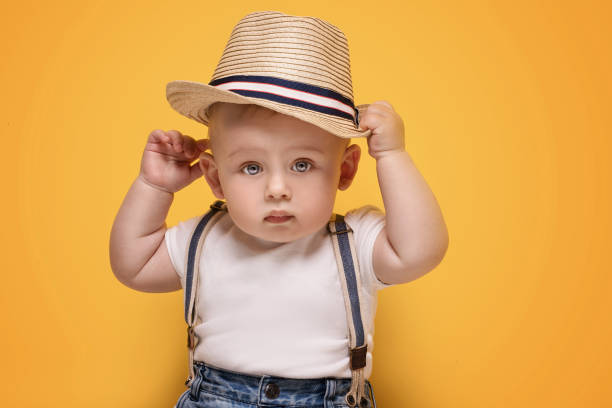 Adorable little baby boy posing. Cute baby boy posing in summer hat on yellow background. Adorable little child in studio. suspenders stock pictures, royalty-free photos & images