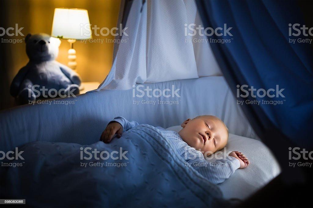 Adorable little baby boy sleeping at night stock photo