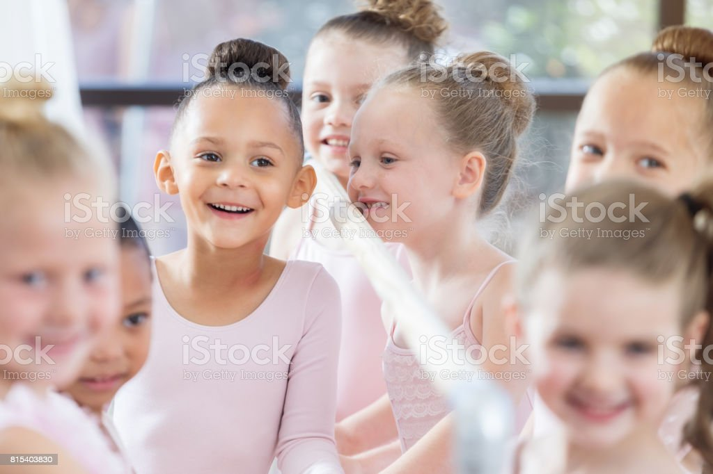 Adorable little ballerina smiles joyfully during class stock photo