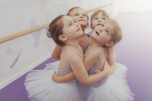 Adorable little ballerinas exercising at ballet school Adorable little girls in leotards and tutu skirts embracing, looking away joyfully. Group of cute young ballerinas having fun after ballet class, copy space. Friendship, childhood, sisterhood concept dance studio stock pictures, royalty-free photos & images