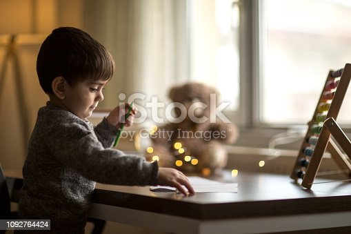 istock Adorable little boy, drawing picture 1092764424