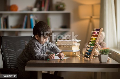 istock Adorable little boy, drawing picture 1092764454