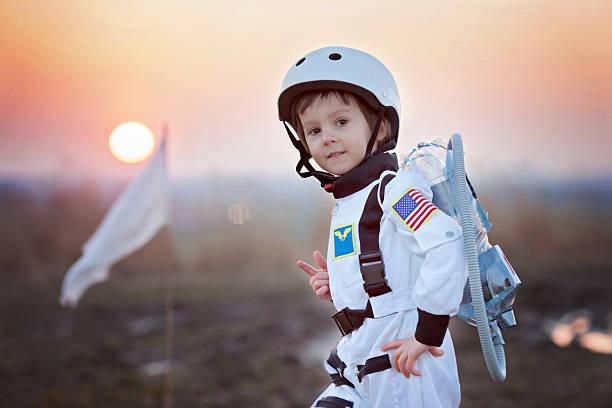 süßen kleinen jungen, das als astronaut, spielen im park - kleine jungen kostüme stock-fotos und bilder