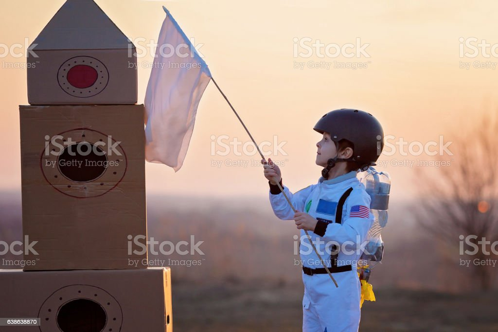 Adorable little boy, dressed as astronaut, playing in the park stock photo