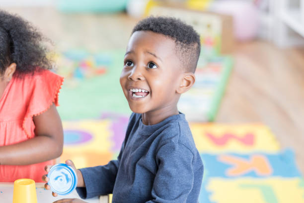 entzückender kleine junge spielt im vorschulalter klassenzimmer - knete spiele stock-fotos und bilder