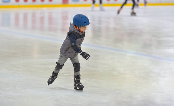Adorable little boy in winter clothes with protections skating on ice rink Adorable little boy in winter clothes with protections skating on ice rink ice skating stock pictures, royalty-free photos & images