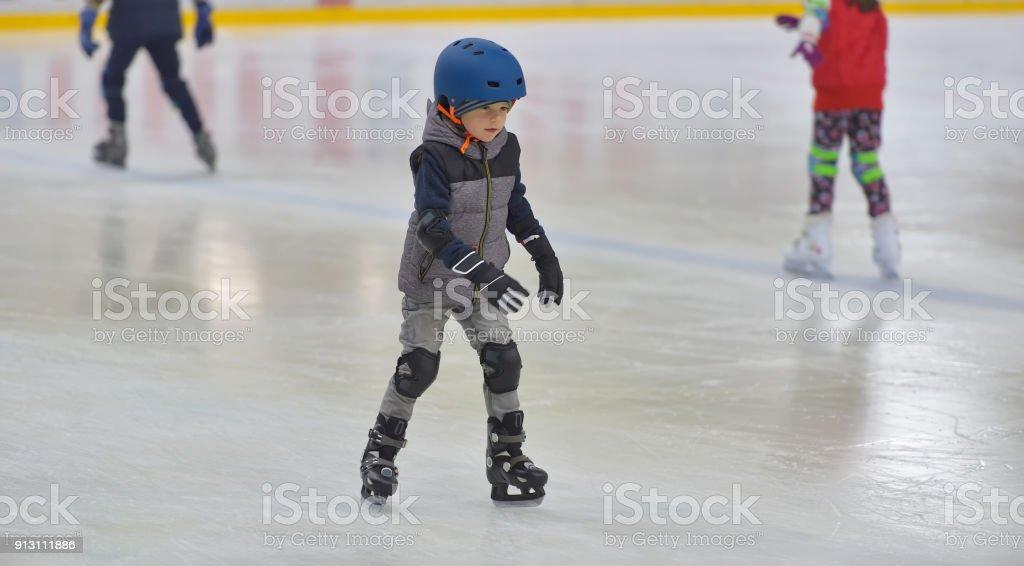 Adorável menino com roupas de inverno com proteções patinar na pista de gelo - foto de acervo