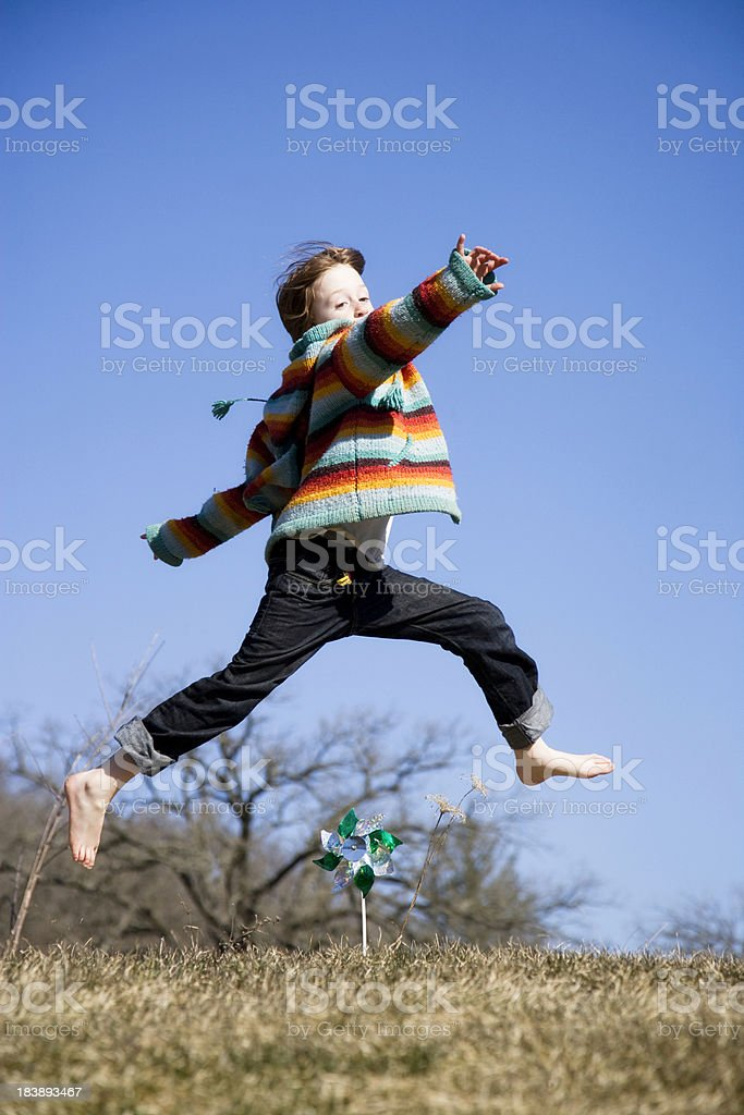 Adorable Little Boy Jumping Over Pinwheel royalty-free stock photo