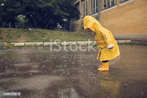 Little boy walking outdoors at rainy autumn day