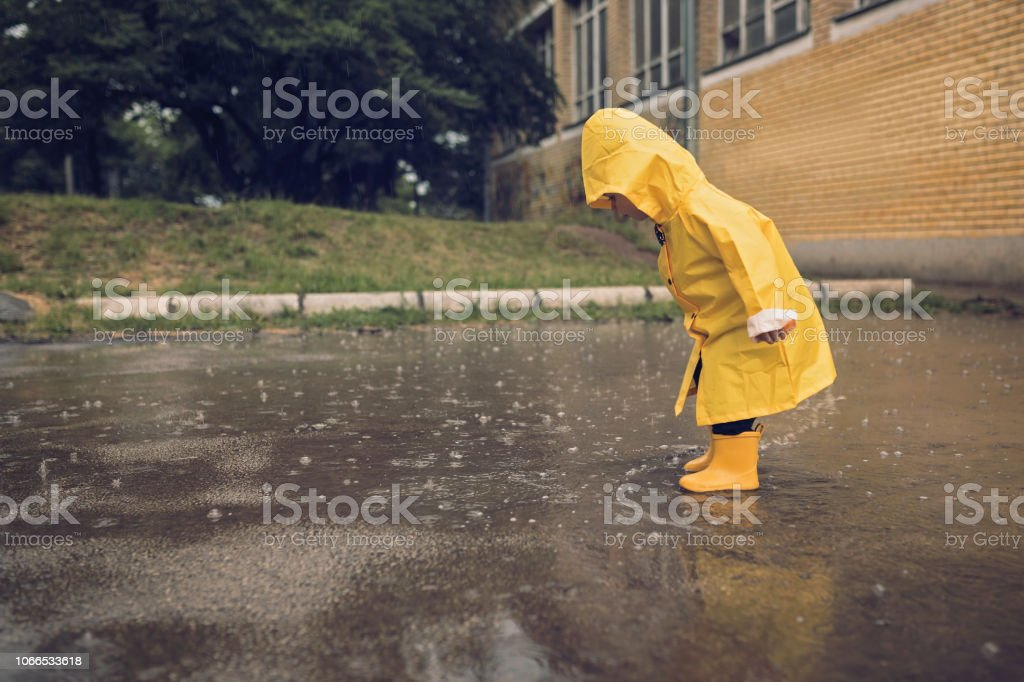 Adorable little boy playing at rainy day stock photo