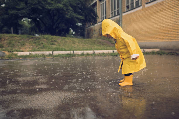 Adorable little boy playing at rainy day Little boy walking outdoors at rainy autumn day waterproof clothing stock pictures, royalty-free photos & images