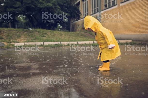 Photo of Adorable little boy playing at rainy day
