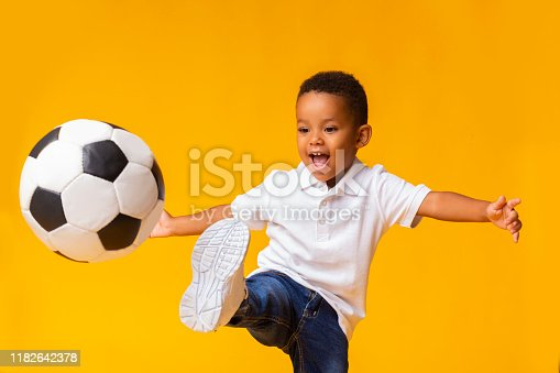 istock Adorable little boy playing football, hitting ball over yellow background 1182642378