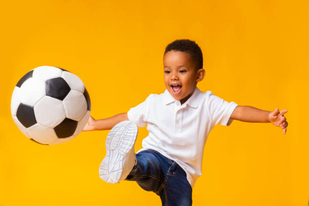 adorable little boy playing football, hitting ball over yellow background - soccer supporter portrait imagens e fotografias de stock