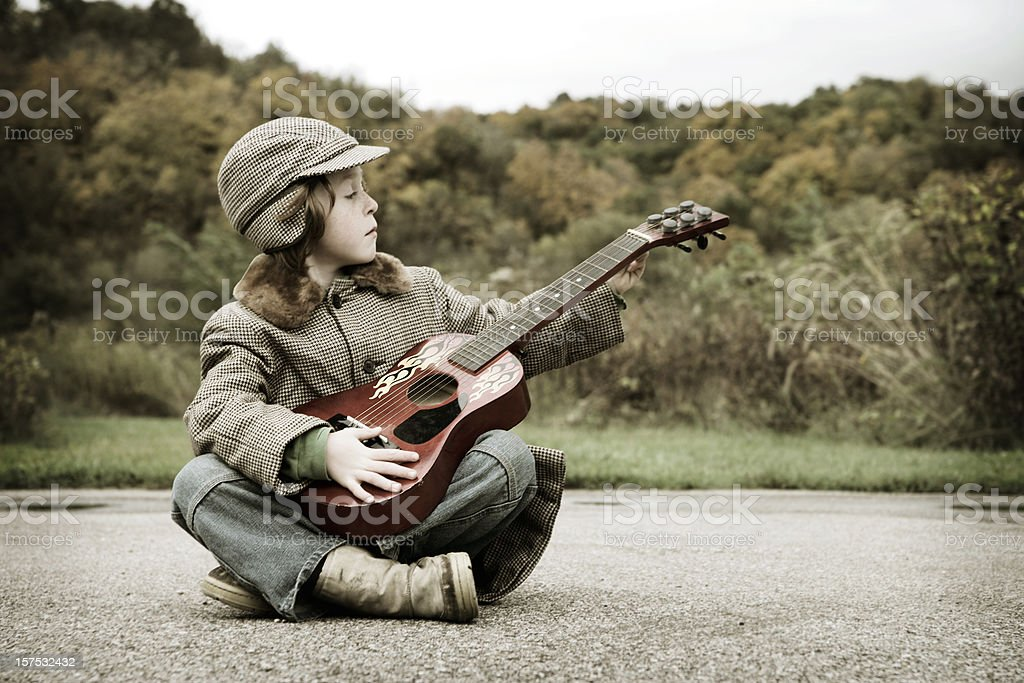 Adorable Little Boy Playing Guitar at Prairie royalty-free stock photo