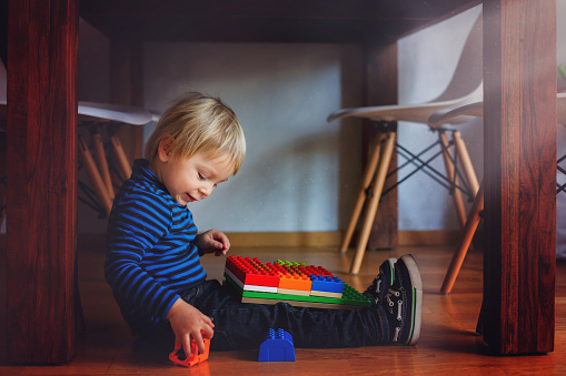 Adorable little boy playing with colorful plastic construction blocks at home, sitting on the floor under the table. Creative games for kids