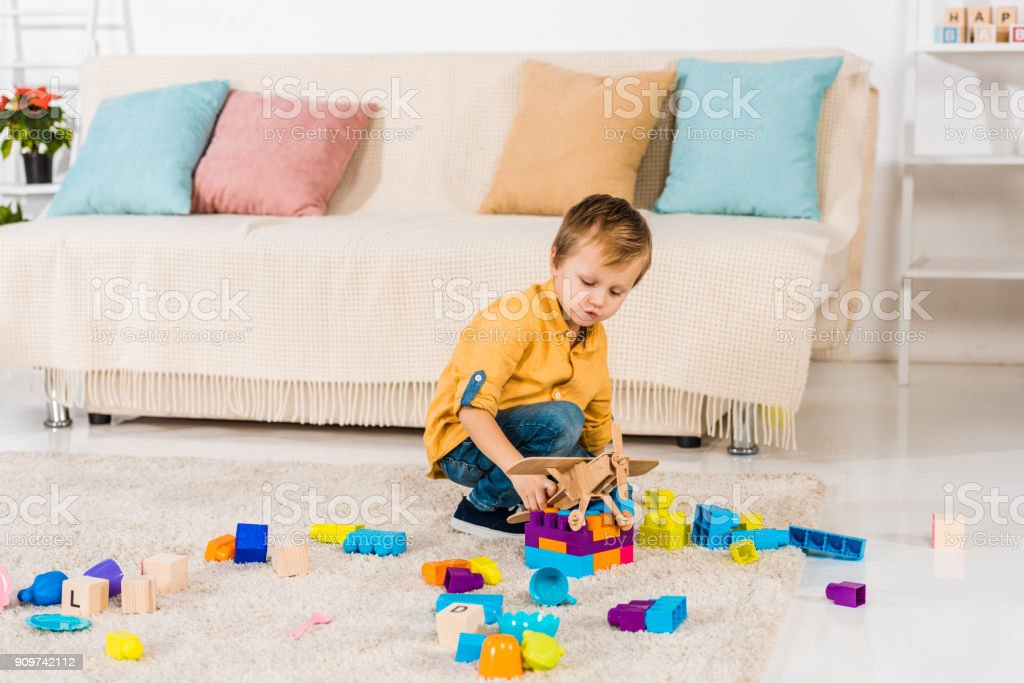 adorable little boy playing with toy airplane and colorful blocks at home stock photo