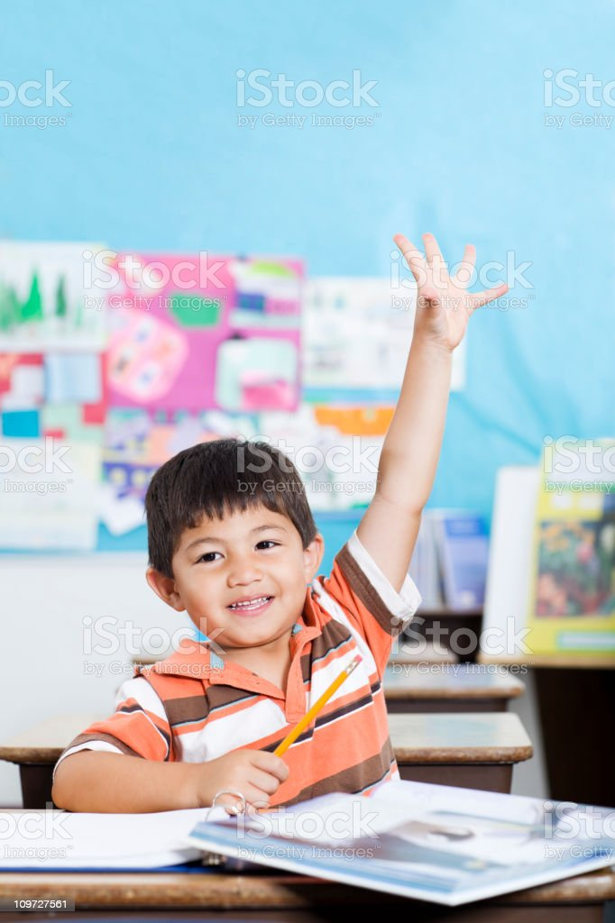 Adorable Little Boy Raising Hand in Elementary Classroom royalty-free stock photo