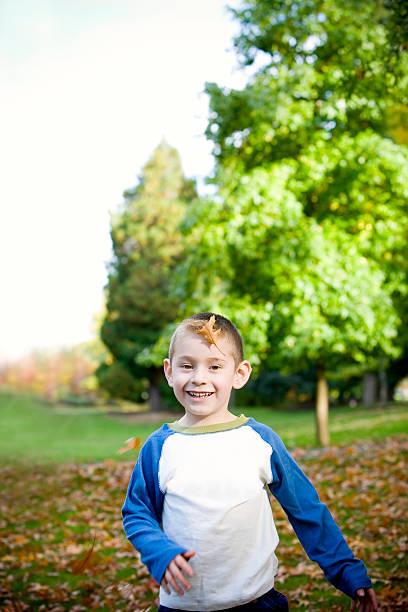 Adorável menino correndo no outono ao ar livre, espaço para texto - foto de acervo