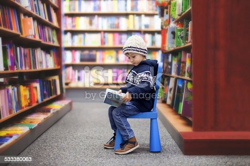 istock Adorable little boy, sitting in a book store 533380063