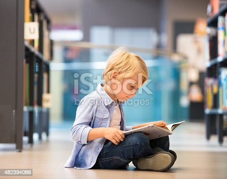 istock Adorable Little Boy Sitting In Library 482394086