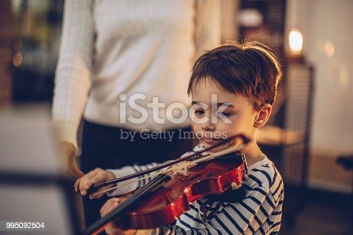 Boy teaching to play violin in music school