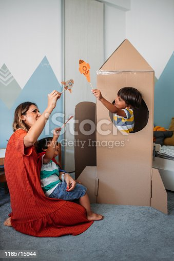 Adorable little boys and their mother playing with cardboard rocket at home.