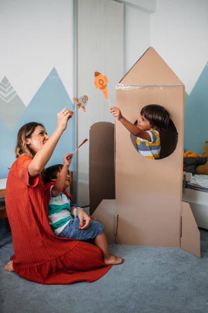 Adorable Little Boys And Their Mother Playing With Cardboard Rocket At Home