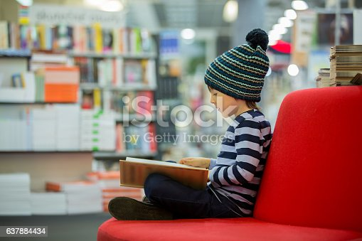 istock Adorable little child, boy, sitting in a book store 637884434