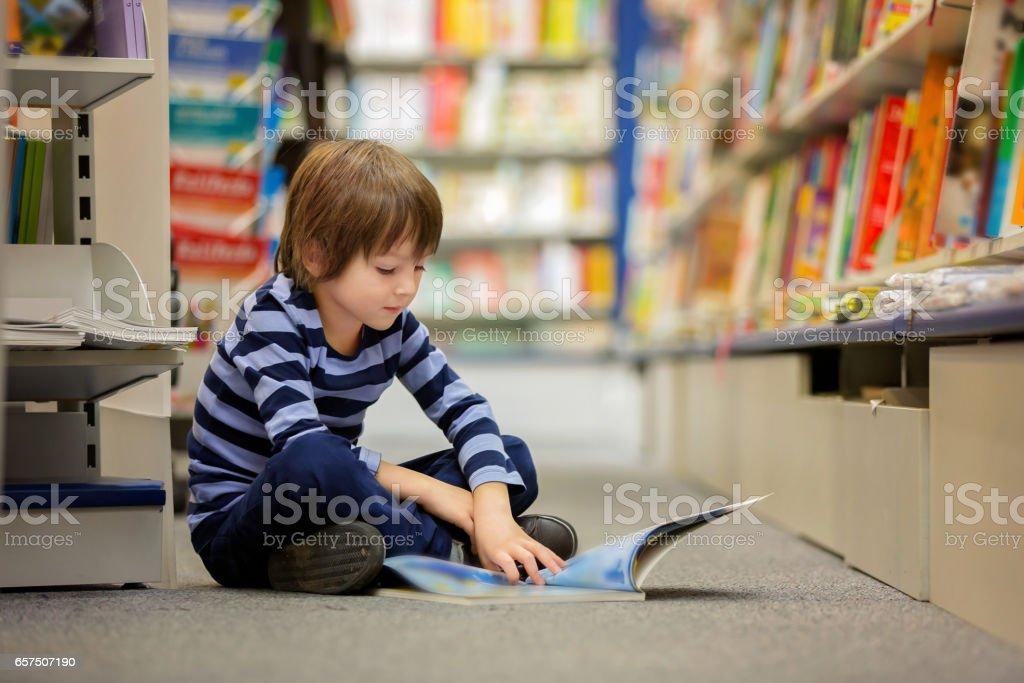 Adorable niño, niño, sentado en una tienda de libros, libros de lectura - foto de stock