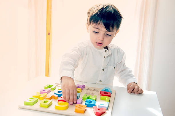 Adorable little child playing with colorful wooden letters – Foto
