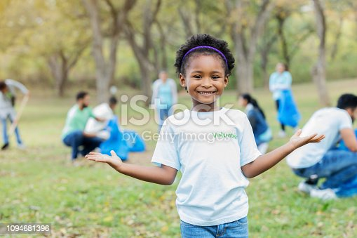An adorable preschool age little girl stands outdoors in a public park.  There are adults picking up litter in the background as she wears a t-shirt that says,