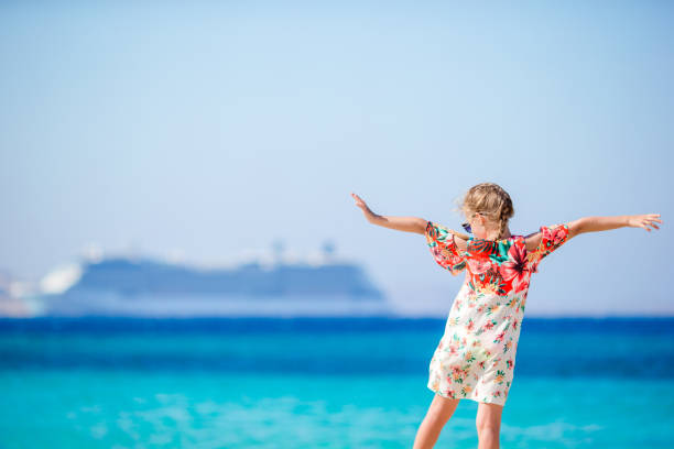 adorable little girl at beach background big cruise lainer in greece - cruise foto e immagini stock