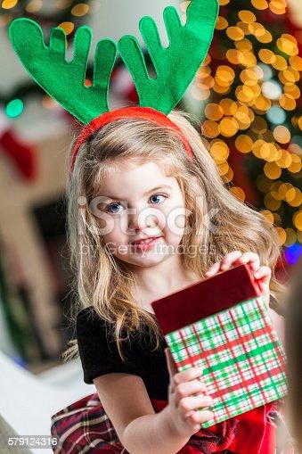 istock Adorable little girl at Christmastime wearing festive headband 579124316